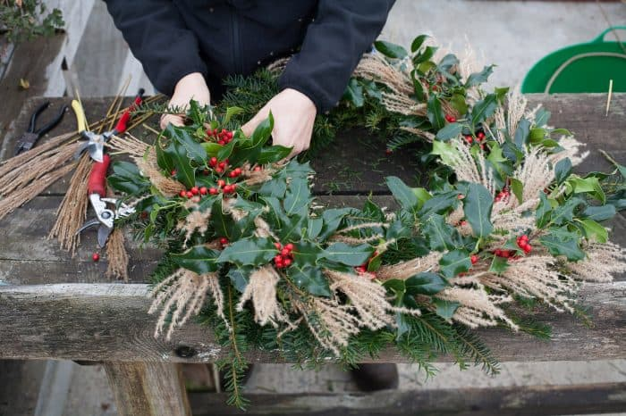 The finishing touches of holly being added to the Christmas wreath